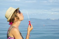 Girl blowing soap bubbles at the beach by the sea wearing straw Royalty Free Stock Photography