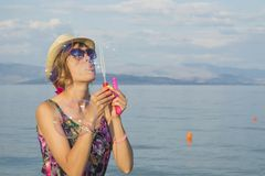 Girl blowing soap bubbles at the beach by the sea wearing straw Stock Photos