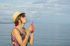 Girl blowing soap bubbles at the beach by the sea wearing straw Stock Photography