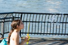 Girl blowing soap bubbles. At the Brooklyn Bridge Promenade in New York City on May 11, 2014 Royalty Free Stock Images