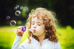 Girl blowing soap bubbles, closeup portrait beautiful curly baby Royalty Free Stock Image
