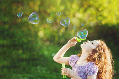 Girl blowing soap bubbles with heart shaped Stock Image