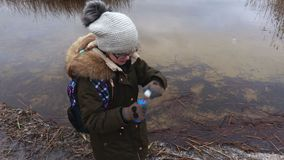 Girl blowing soap bubbles near the lake stock video footage