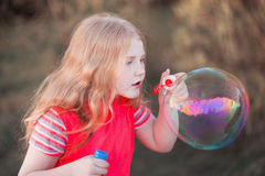 Girl blowing soap bubbles outdoor Royalty Free Stock Images