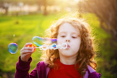 Girl blowing soap bubbles in the rays of the sun. Toning for ins Stock Photos