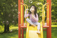 Girl blowing soap bubbles on slide. Cute little girl sitting on the slide while blowing soap bubbles, shot at the playground Royalty Free Stock Photography