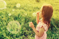 Girl is blowing a soap bubbles in summer field Stock Photography