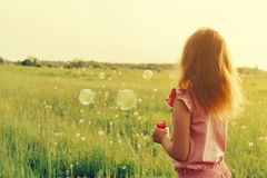 Girl is blowing a soap bubbles in summer Royalty Free Stock Photography