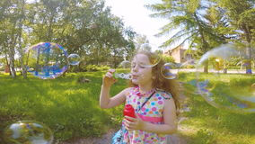 Girl blowing soap bubbles in summer park. Happy girl blowing soap bubbles in summer park stock video footage