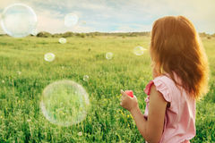 Girl blowing soap bubbles in summer at sunny day. Little girl in pink dress blowing soap bubbles on summer meadow at sunny day, rear view. Image with sunlight Royalty Free Stock Photos