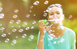 Girl blowing soap bubbles in sunlit park. Stock Image