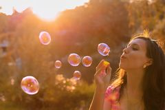 Girl blowing soap bubbles at sunset Stock Photography