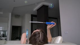 Girl blowing soap bubbles up. Lying on the sofa stock video footage