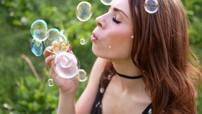 Girl blowing soap bubbles. Young beautiful woman sits on the grass in the park and plays with bubbles. Slow motion video stock video footage