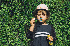 Girl blowing soap bubbles Stock Photos