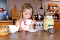 Girl blowing to cup of hot drink Royalty Free Stock Image