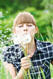 Girl blowing to the dandelion Royalty Free Stock Images
