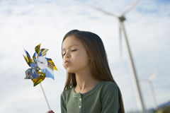 Girl Blowing Toy Windmill Royalty Free Stock Image