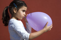 Girl blowing up balloon Royalty Free Stock Photography
