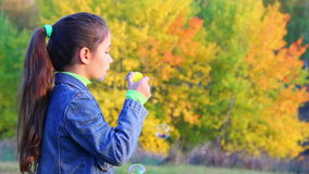 Girl blowing up a soap bubbles stock footage