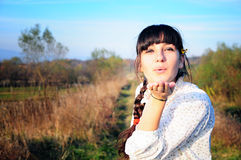Girl blownig a kiss. Autumn light outside Stock Images