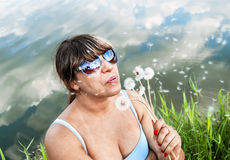 Girl blows away the fluff with dandelions Stock Images