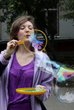 Girl blows big soap bubbles Stock Photo