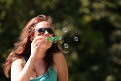Girl blows bubbles Stock Images