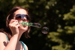 Girl blows bubbles Stock Photo