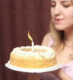 Girl blows on a candle Stock Images