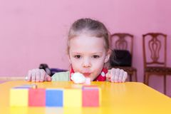Girl blows cotton ball into the goal Royalty Free Stock Images