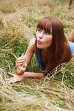 Girl blows on dandelion Stock Images