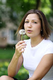 Girl blows on a dandelion Stock Image