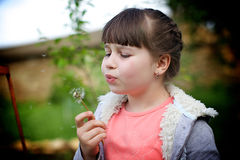 girl blows on a dandelion Royalty Free Stock Photo
