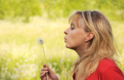 Girl blows on dandelion and desire Royalty Free Stock Photography