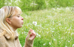 Girl blows on dandelion and thinks desire 5 Stock Photo