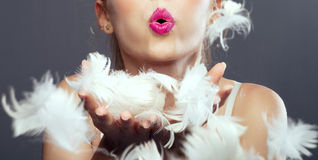 Girl blows in feathers. Stock Photography