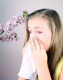 Girl blows her nose with handkerchief, cherry blossoms Royalty Free Stock Photography