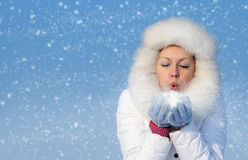 Girl blows off snowflakes from the hand. Blue sky, falling snow Stock Image