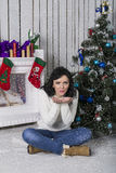 The girl. Blows off snowflakes near the Christmas tree Stock Images