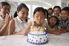Girl Blows Out Candles At Family Birthday Celebration Royalty Free Stock Photography