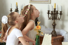 Girl blows out the candles on the mantelpiece. Happy little girls twins blew out the candles in the candlestick which stands on the mantelpiece Royalty Free Stock Images