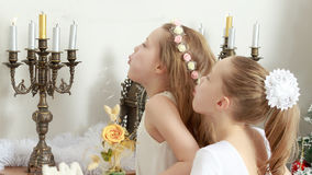 Girl blows out the candles on the mantelpiece. Happy little girls twins blew out the candles in the candlestick which stands on the mantelpiece Royalty Free Stock Photo