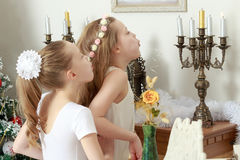Girl blows out the candles on the mantelpiece. Happy little girls twins blew out the candles in the candlestick which stands on the mantelpiece Stock Images