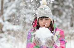 Girl blows snow from hands Stock Photo