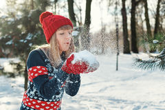 Girl blows snow with mittens and make a wish stock photography