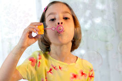 Girl blows soap bubble Royalty Free Stock Image