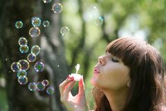 Girl blows soap bubbles. In park Royalty Free Stock Photography