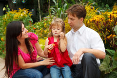 Girl blows soap bubbles in garden with parents Stock Photo