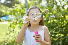 Girl blows soap bubbles in the summer Stock Image